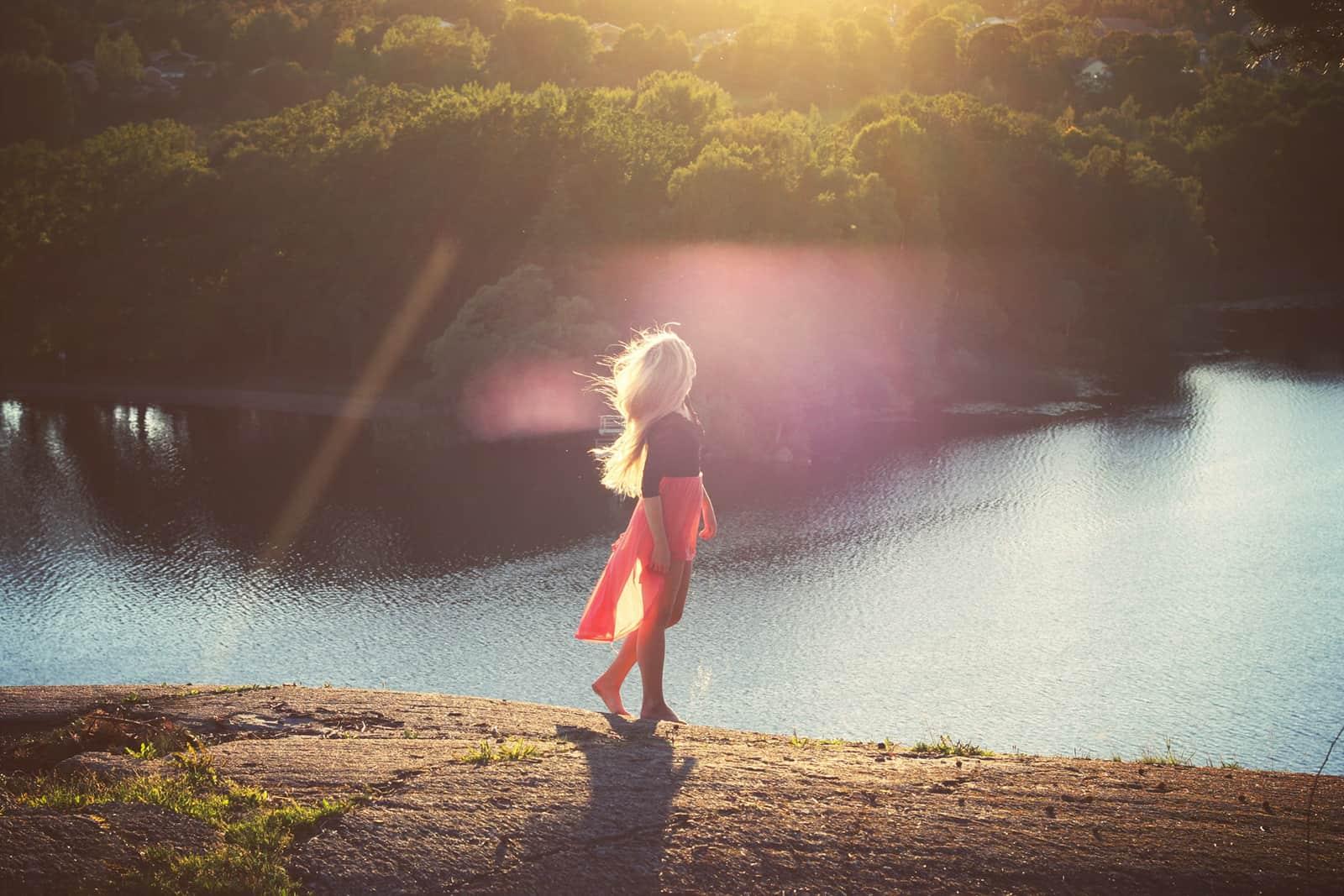Frau, die allein in der Nähe des Sees während des Sonnenuntergangs geht