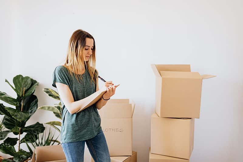Frau, die auf einen Karton schreibt, der durch Kartonschachteln umgeben ist