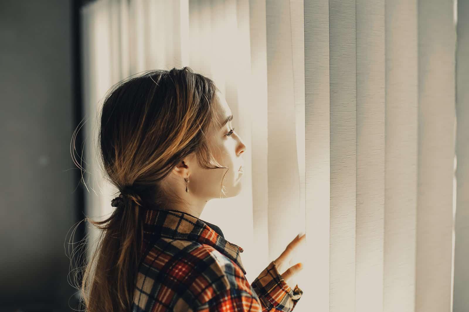 Frau, die durch die Jalousien des Fensters schaut und denkt
