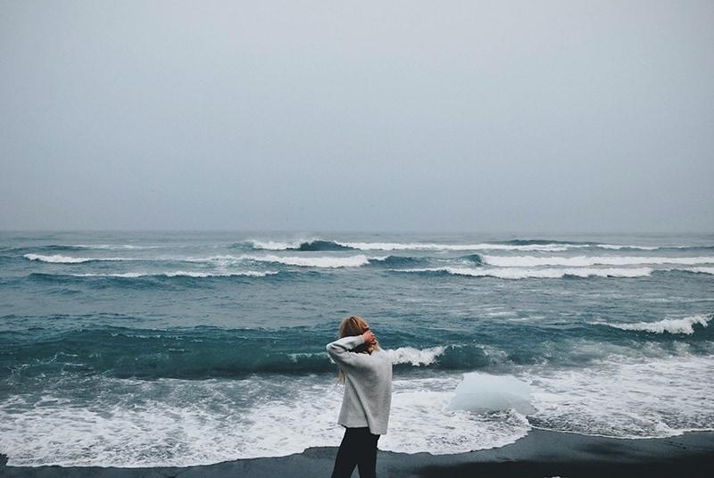 Frau, die während eines Seesturms neben der Küste geht