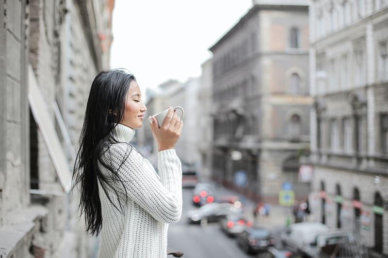 Frau hält eine Tasse Kaffee, während sie die Augen auf dem Balkon schließt