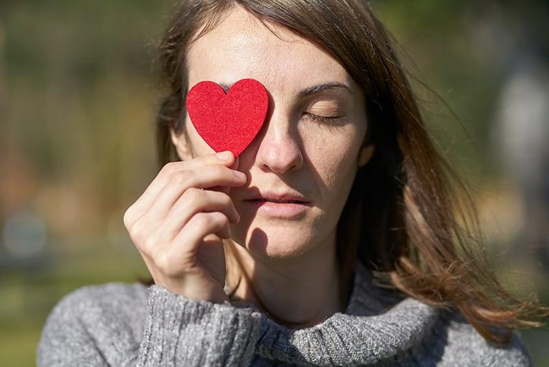 Frau hält herzförmigen Ausschnitt und bedeckt ihr rechtes Auge damit