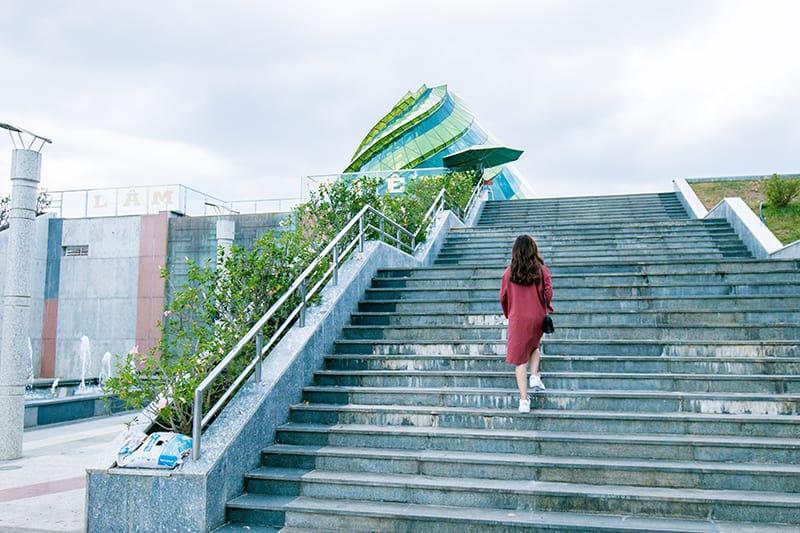 Frau im roten Kleid klettert auf einer Treppe in der Nähe der Gebäude