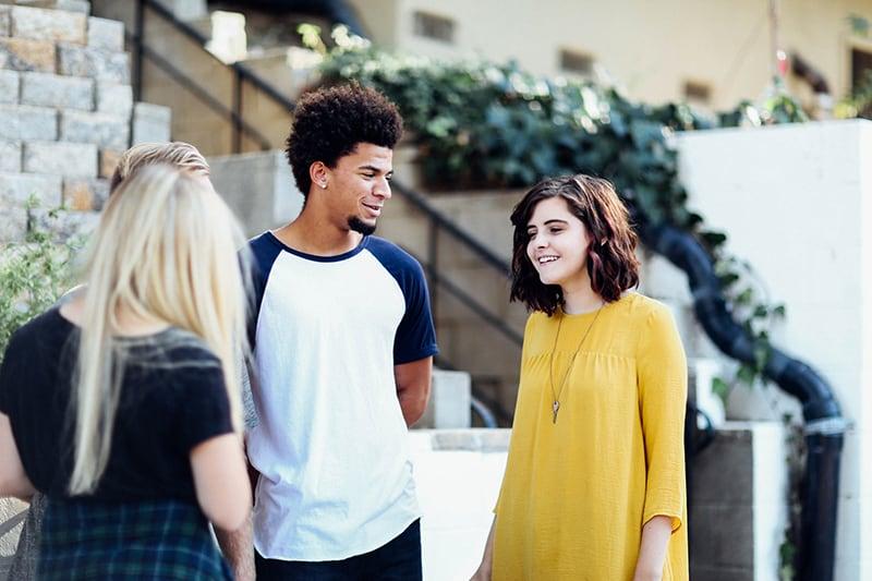 Frau in der gelben Bluse, die mit einem Mann spricht, während sie mit Freundinnen steht