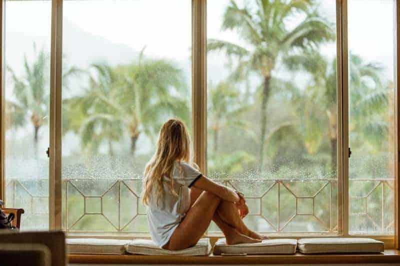 Frau-in-weiß-Kissen-sitzen-in der Nähe von Glasfenster