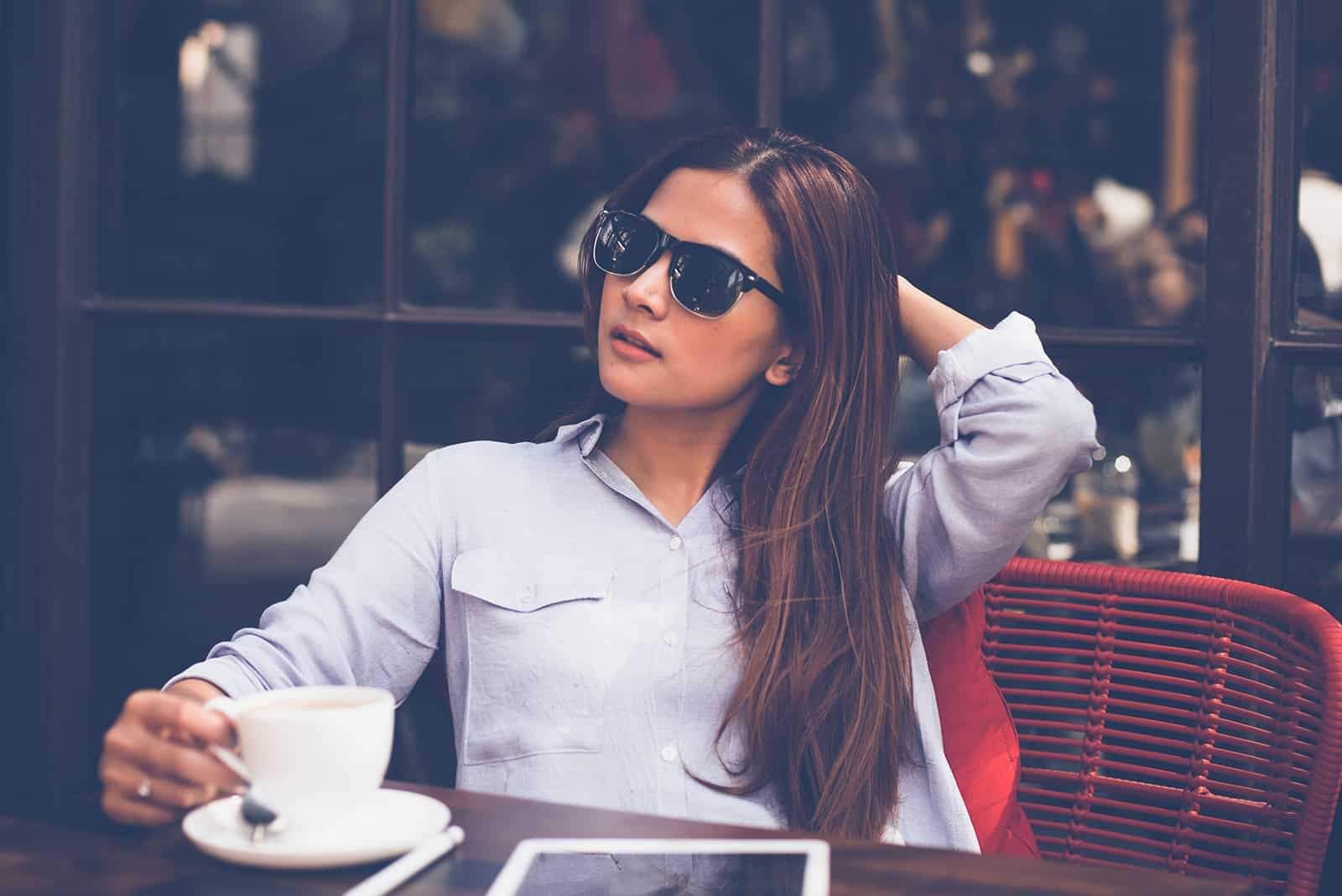 Frau mit Sonnenbrille sitzt Kaffee allein im Café trinkend