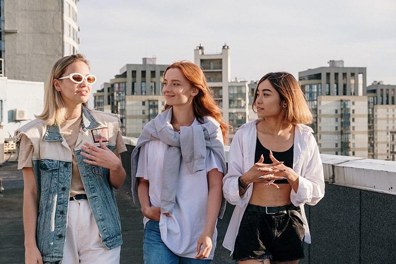 Frau mit Sonnenbrille im Gespräch mit ihren beiden Freundinnen beim gemeinsamen Gehen