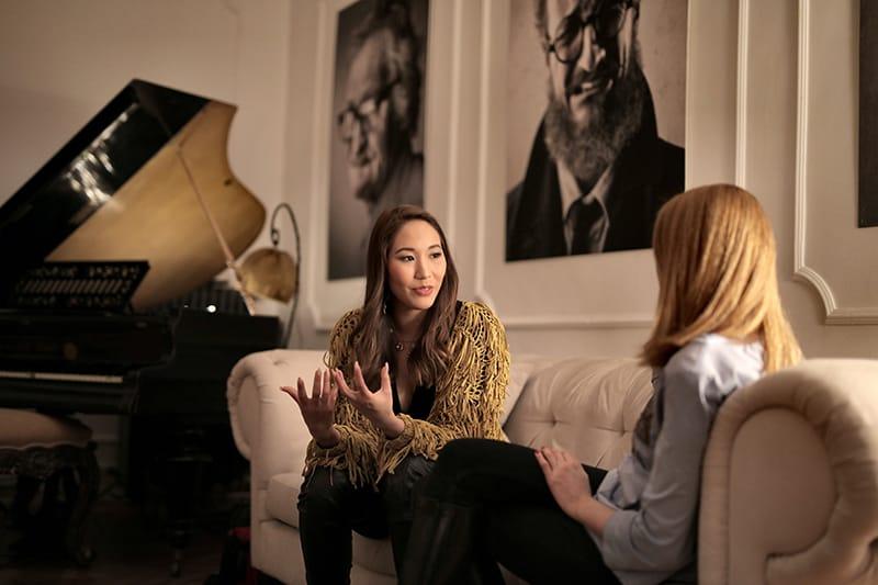 Frau mit langen braunen Haaren spricht mit ihrer Freundin, während sie auf der Couch sitzt