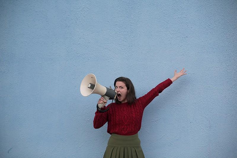 Frau schreit in einen Lautsprecher und hebt die linke Hand