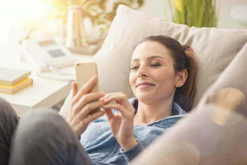 Frau sitzt zu Hause und tippt am Telefon