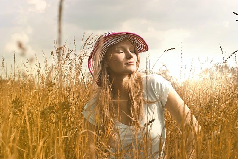 Frau stand auf dem Feld und schloss die Augen