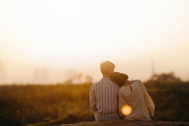 Frau, die Kopf auf ihren Freund stützt, während sie während des Sonnenuntergangs auf dem Boden sitzt