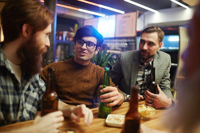 Gruppe männlicher Freunde, die in der Kneipe sitzen und reden