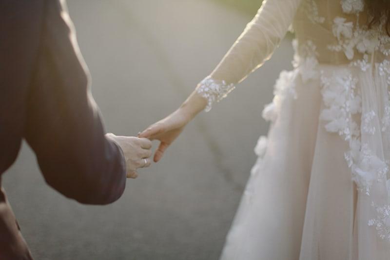 frisch verheiratetes Händchenhalten beim Gehen auf der Straße