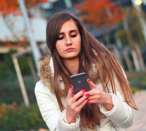 eine verärgerte Frau, die ein Smartphone betrachtet