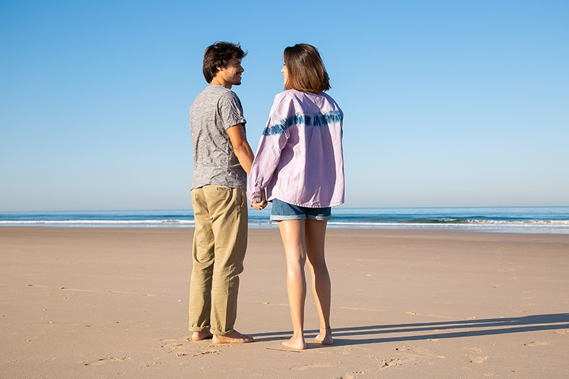 Liebespaar Händchenhalten beim Stehen am Strand