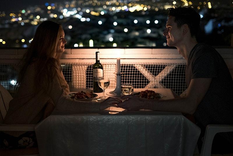 Liebespaar Händchenhalten beim Sitzen auf dem Tisch während des romantischen Abendessens