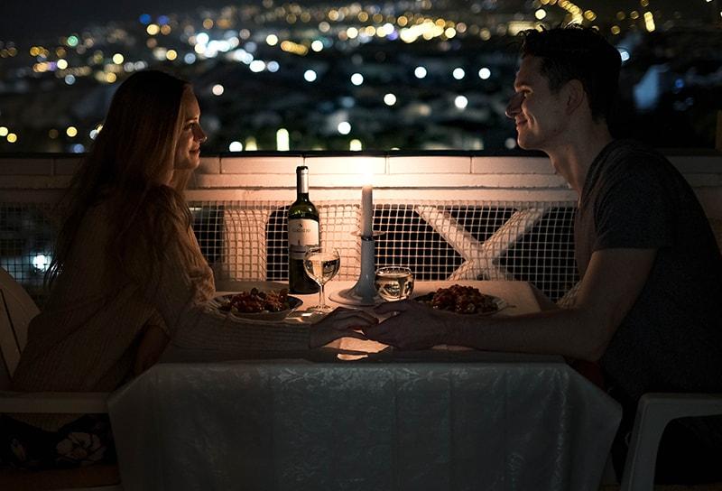 Liebespaar, das abends auf dem Balkon speist und sich an den Händen hält