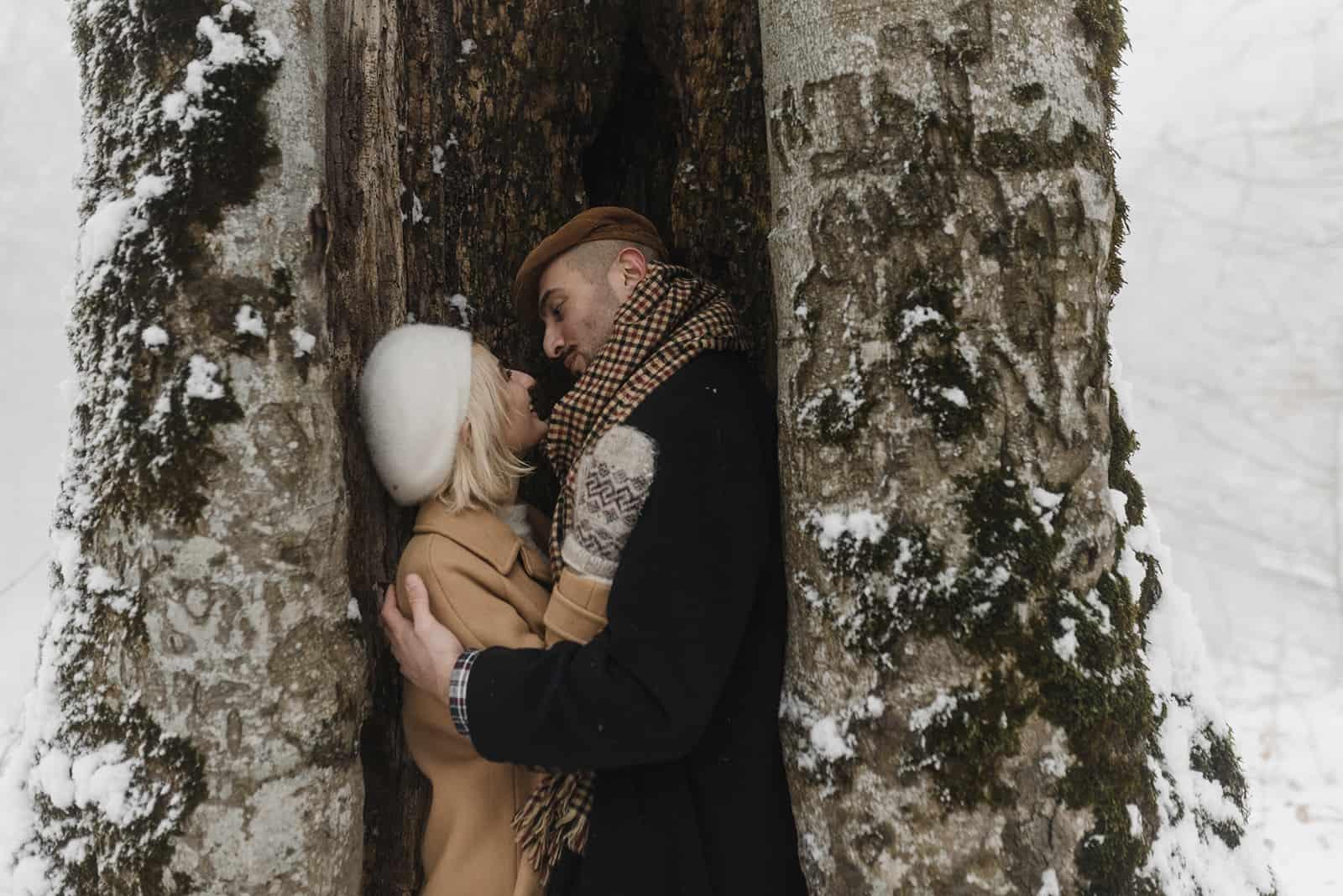 Liebespaar, das an einem verschneiten Tag in der Nähe des Baumes umarmt