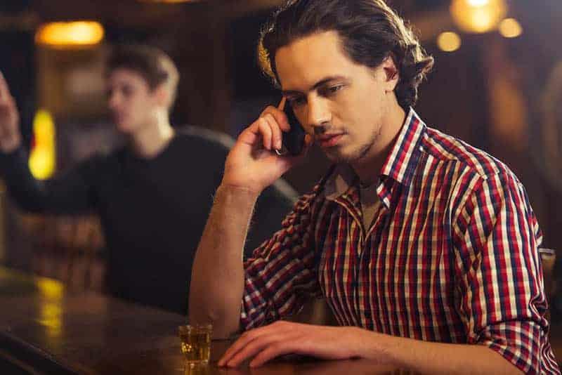 Mann, der an der Bar telefoniert