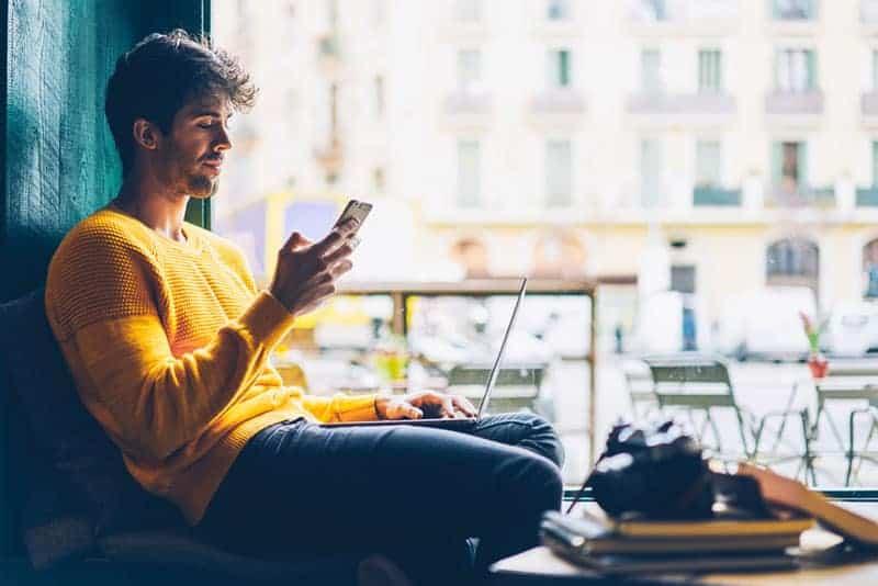 Mann, der auf seinem Telefon im Café tippt