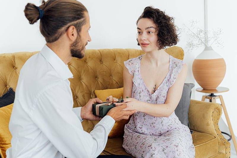 Mann, der seiner Freundin ein Geschenk gibt, während er auf der Couch sitzt
