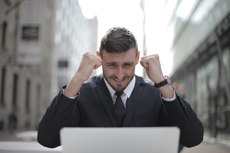 Mann in einem schwarzen Anzug erreicht eine Leistung, die vor dem Laptop sitzt