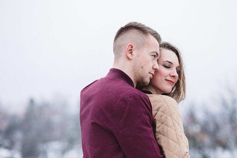 Mann, der eine Frau von hinten umarmt, während er draußen steht