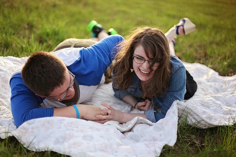 Mann und Frau lachen, während sie auf der weißen Matte im Park liegen