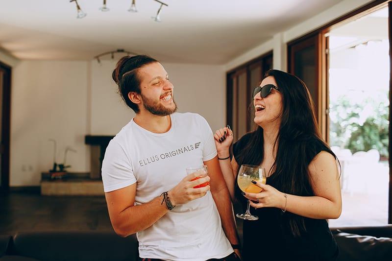 Mann und Frau lachen zusammen, während sie Getränke im Haus halten