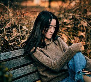 traurige Frau, die alleine auf der Bank sitzt