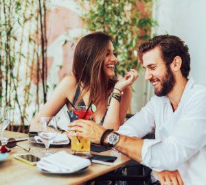ein fröhliches Paar sitzt und trinkt