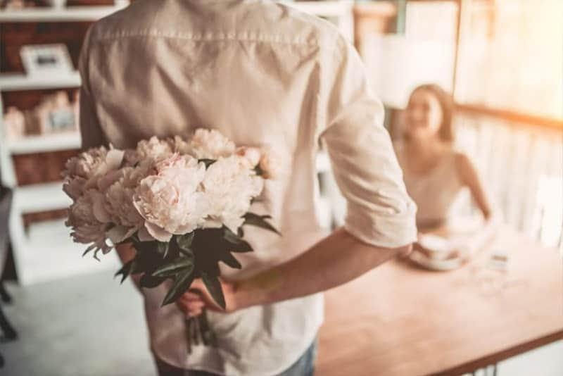 ein Mann, der hinter seinem Rücken einen Blumenstrauß in der Hand hält