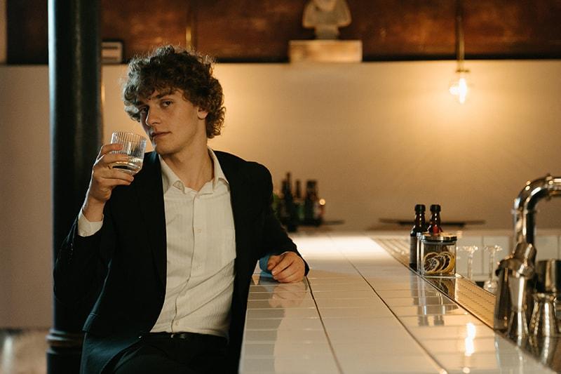 Mann hält Getränk an der Theke sitzen