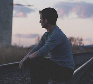 ein Mann sitzt auf Schienen