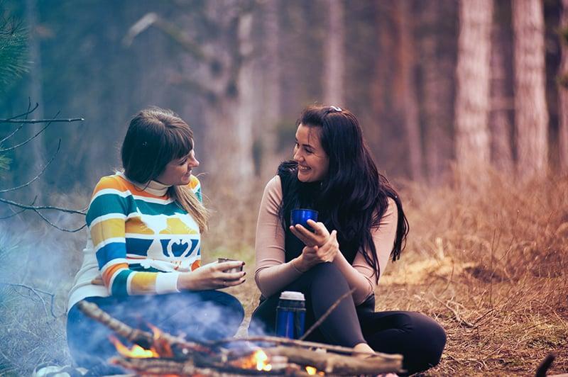 Zwei Frauen sitzen auf dem Boden neben dem Lagerfeuer und unterhalten sich