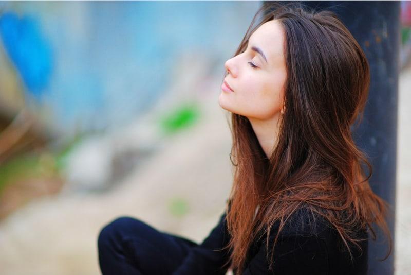 achtsame Frau, die mit geschlossenen Augen sitzt