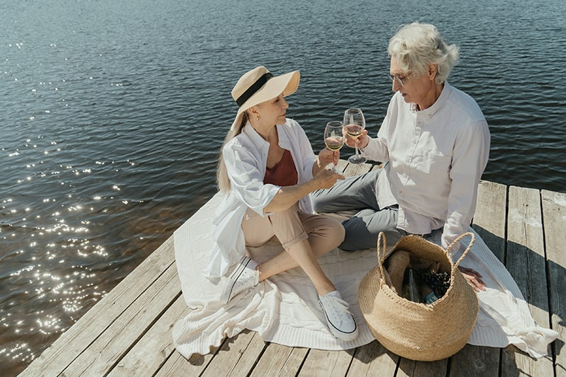 älteres Paar, das Wein auf dem Dock nahe dem Meer trinkt