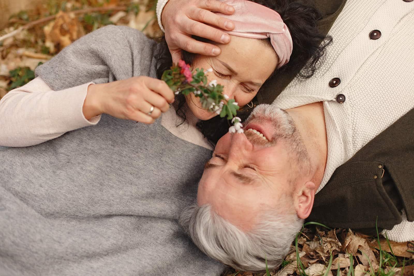 älteres verliebtes Paar, das im Gras liegt und kuschelt