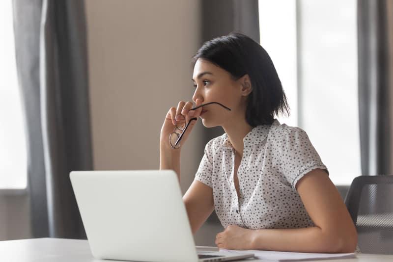 besorgte Frau, die denkt, während sie am Arbeitstisch sitzt