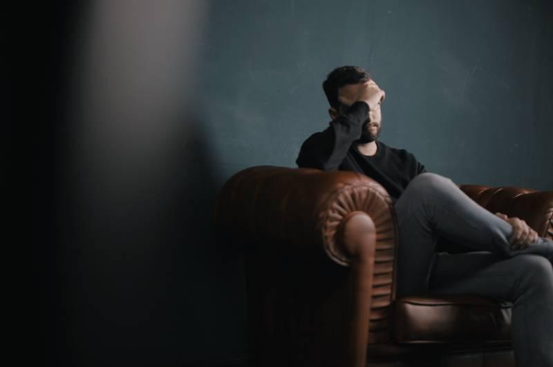besorgter Mann, der auf dem Sofa sitzt