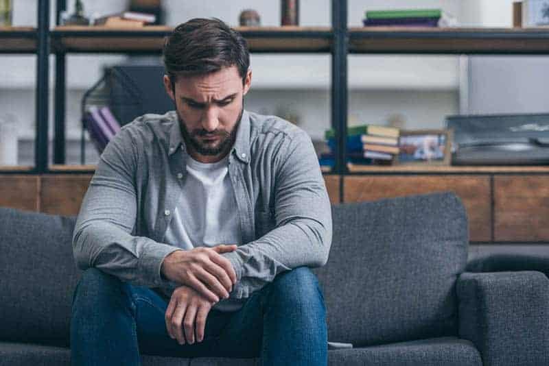 besorgter Mann, der auf der Couch sitzt