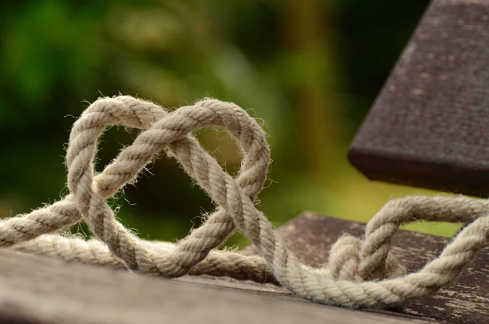 braunes Seil verheddert und auf brauner Holzschiene herzförmig geformt