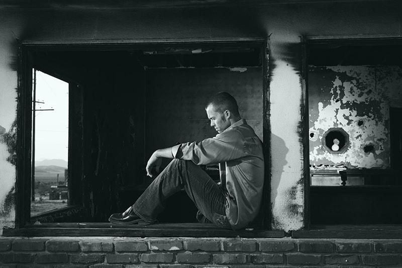 depressiver Mann sitzt auf der Fensterbank eines alten Gebäudes