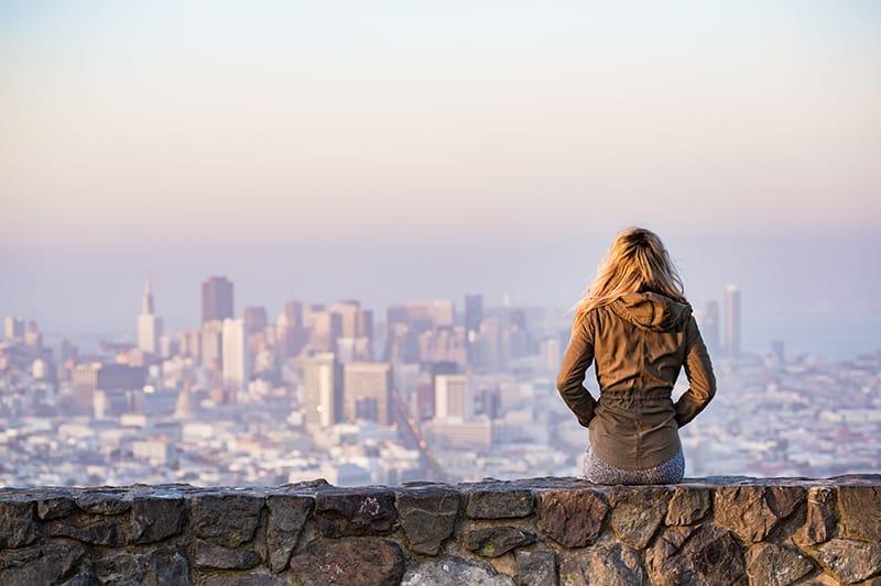 Die Frau sitzt auf der Felsplattform und betrachtet eine Stadt