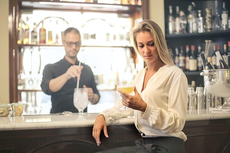 Die nachdenkliche Frau saß an der Theke und hielt ein Glas mit einem Getränk in der Hand
