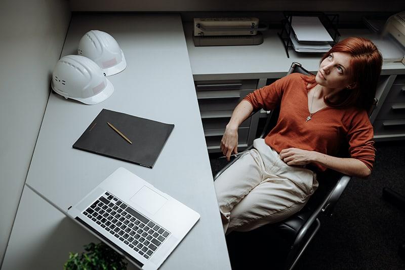 die nachdenkliche Frau sitzt auf dem Stuhl, während sie am Laptop arbeitet