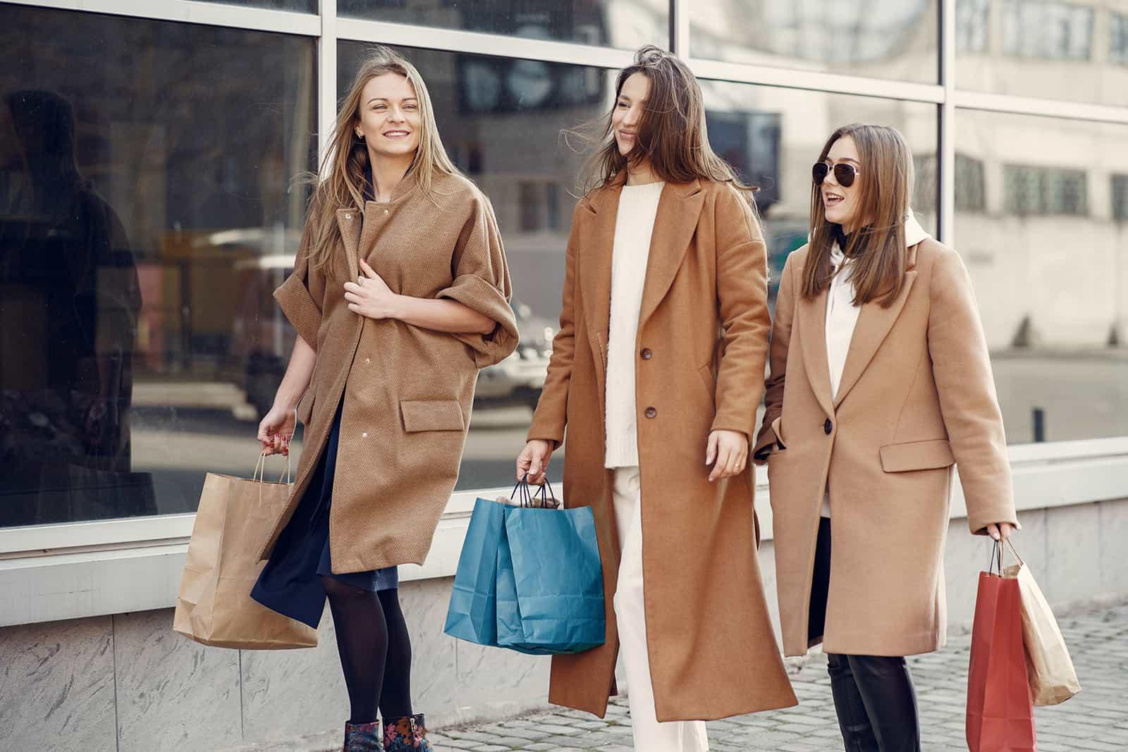 drei Freundinnen, die Einkaufstaschen halten, während sie auf dem Bürgersteig gehen