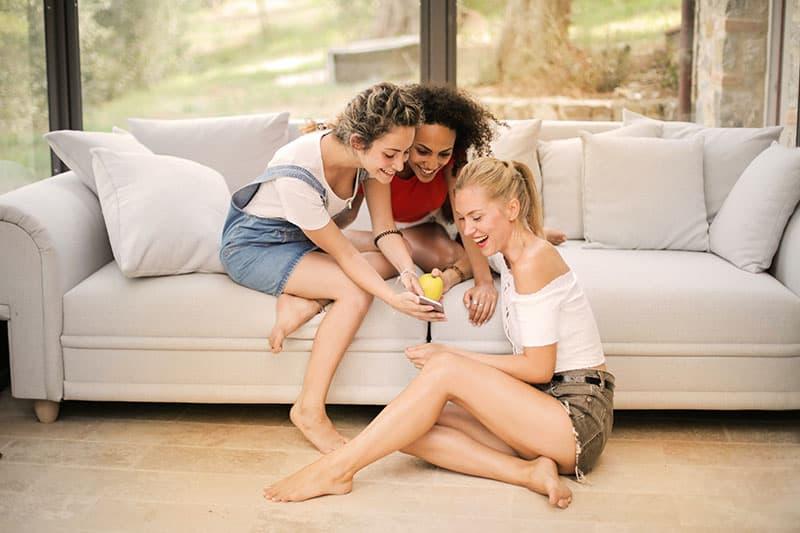 drei lächelnde Frauen, die ein Smartphone betrachten, während sie im Wohnzimmer sitzen