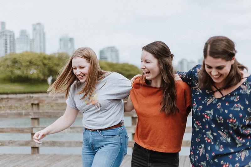 drei lächelnde Freundinnen, die auf dem Holzsteg gehen und sich umarmen
